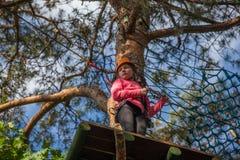Muchacha que sube en el parque de la aventura, parque de la cuerda Imágenes de archivo libres de regalías