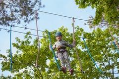 Muchacha que sube en el parque de la aventura, parque de la cuerda Imagenes de archivo