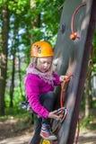 Muchacha que sube en el parque de la aventura, parque de la cuerda Foto de archivo libre de regalías
