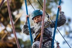Muchacha que sube en el parque de la aventura, parque de la cuerda Imagen de archivo libre de regalías