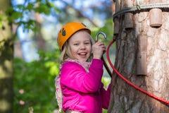 Muchacha que sube en el parque de la aventura, parque de la cuerda Fotografía de archivo libre de regalías