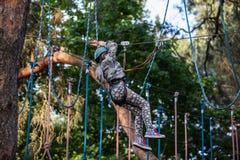 Muchacha que sube en el parque de la aventura, parque de la cuerda Fotos de archivo