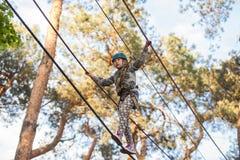 Muchacha que sube en el parque de la aventura, parque de la cuerda Fotografía de archivo