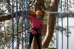Muchacha que sube en parque de la aventura Fotografía de archivo