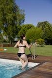 Muchacha que sube la escala fuera de una piscina Fotografía de archivo libre de regalías