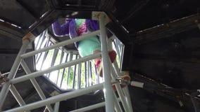 Muchacha que sube para arriba la escalera en patio almacen de metraje de vídeo
