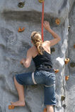 Muchacha que sube para arriba una pared artificial de la roca. Imagen de archivo