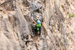 Muchacha que sube una pared de la roca fotos de archivo