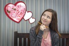 Muchacha que sueña despierto al lado de corazones flotantes con las rosas rosadas Fotos de archivo libres de regalías