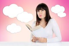 Muchacha que sueña despierto mientras que lee un libro y mira para arriba en un rosa fotografía de archivo libre de regalías