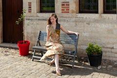 Muchacha que sueña en el sol en un banco Foto de archivo libre de regalías