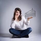 Muchacha que sueña sobre la consumición de la torta Foto de archivo
