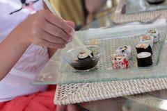 Muchacha que sumerge el sushi imagen de archivo libre de regalías