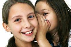Muchacha que susurra un secreto Foto de archivo libre de regalías