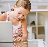 Muchacha que tapa el cable del Internet en la computadora portátil Foto de archivo libre de regalías