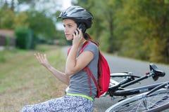 Muchacha que tiene accidente de la bici que invita al tel?fono imagen de archivo libre de regalías