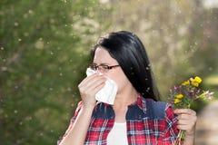 Muchacha que tiene alergia y que estornuda en tejido Fotos de archivo