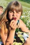 Muchacha que tiene gusto de la fresa Foto de archivo