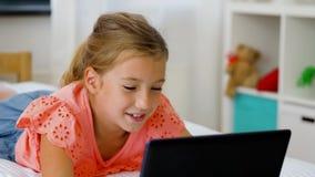 Muchacha que tiene llamada del vide en la tableta en casa almacen de video