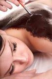 Muchacha que tiene máscara del bodyl del chocolate. fotos de archivo