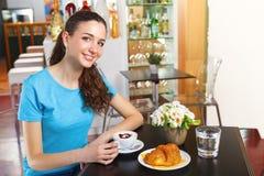 Muchacha que tiene un descanso para tomar café con capuchino Foto de archivo