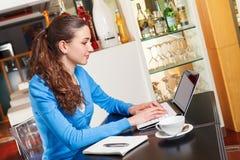 Muchacha que tiene un descanso para tomar café y que trabaja en un ordenador Fotografía de archivo