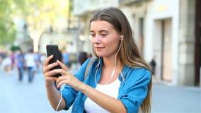 Muchacha que tiene una llamada video en la calle