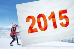 Muchacha que tira de los números 2015 en una bandera Foto de archivo