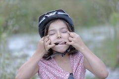 Muchacha que tira de una cara divertida fotos de archivo
