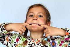 Muchacha que tira de una cara tonta Imágenes de archivo libres de regalías
