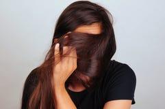 Muchacha que tira del pelo a través de la cara Fotos de archivo