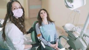 Muchacha que tira reducida-para arriba que miente en la silla dental, sonriendo Un doctor de la mujer va a perforar su diente de  metrajes