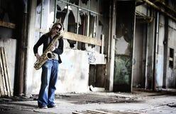 Muchacha que toca el saxofón en pasillo viejo de la fábrica. fotografía de archivo libre de regalías