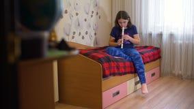 Muchacha que toca la flauta en su cama almacen de video