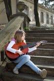 Muchacha que toca la guitarra al aire libre en el parque en Sunny Spring Day Imagen de archivo