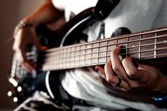 Muchacha que toca la guitarra baja interior en cierre del sitio oscuro para arriba Imagen de archivo libre de regalías