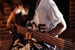 Muchacha que toca la guitarra baja interior en sitio oscuro Imagen de archivo libre de regalías