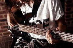 Muchacha que toca la guitarra baja interior en sitio oscuro Fotos de archivo libres de regalías