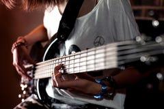 Muchacha que toca la guitarra baja interior en sitio oscuro Imagen de archivo