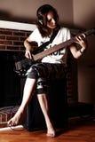 Muchacha que toca la guitarra baja interior en sitio oscuro Imagenes de archivo