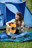 Muchacha que toca la guitarra contra la tienda Foto de archivo libre de regalías