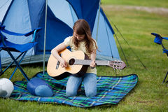 Muchacha que toca la guitarra contra la tienda azul Imágenes de archivo libres de regalías