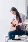 Muchacha que toca la guitarra en casa Foto de archivo libre de regalías