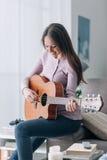 Muchacha que toca la guitarra en casa Fotografía de archivo