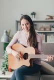 Muchacha que toca la guitarra en casa Imagen de archivo