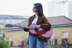 Muchacha que toca la guitarra en escena urbana Foto de archivo