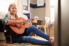 Muchacha que toca la guitarra en su dormitorio Foto de archivo libre de regalías