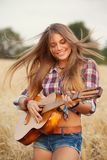Muchacha que toca la guitarra en un campo de trigo Imagenes de archivo