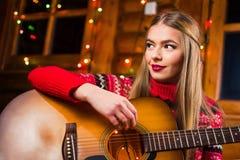 Muchacha que toca la guitarra en una cabaña de madera imagen de archivo