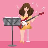 Muchacha que toca la guitarra que compone el acorde musical con el soporte de la nota Foto de archivo libre de regalías